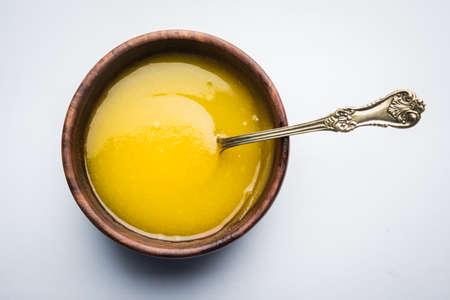 Ghee oder geklärter Butter schließen oben in der hölzernen Schüssel und im silbernen Löffel, selektiver Fokus Standard-Bild