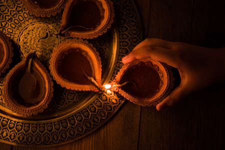 Happy diwali - Hand holding or lighting or arranging diwali diya or clay lamp in brass plate, selective focus