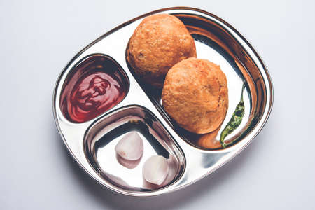 Kachori or Kachauri or kachodi - Indian deep fried junk but tasty food or snacks served in stainless steel plate over white background with tomato ketchup and green fried chilly, selective focus Stock Photo
