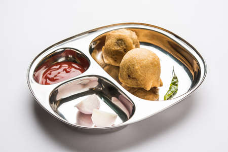 Aloo Bonda, Batata Vada or Alubonda - Indian deep fried junk but tasty food or snacks served in stainless steel plate over white background with tomato ketchup and green fried chilly, selective focus Stock Photo