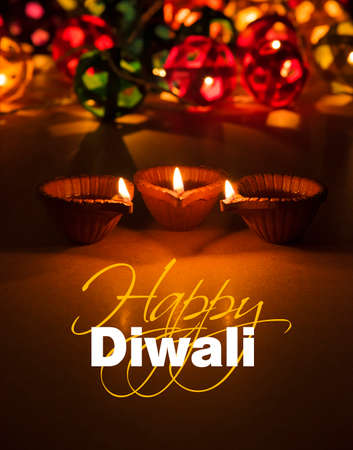 Stock photo of diwali greeting card showing illuminated diya or oil lamp or panti with Happy Diwali text