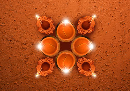 Stock photo of diwali greeting card showing top view of many illuminated diyas or oil lamps or panti forming shape of Diya with Happy Diwali text Stock Photo