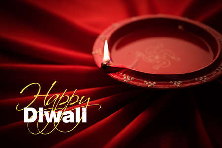 Happy diwali greeting card - Big illuminated diwali diya or clay lamp placed over satin cloth creating rays effect in cloth, moody lighting, selective focus Stock Photo