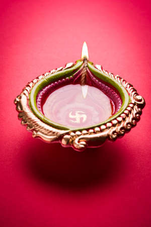 Big illuminated designer diwali diya or clay lamp placed over red background, moody lighting, selective focus