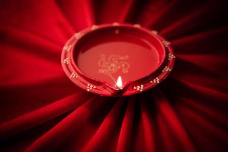 warm cloth: Big illuminated diwali diya or clay lamp placed over satin cloth creating rays effect in cloth, moody lighting, selective focus
