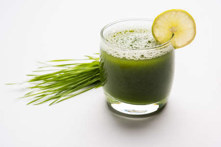 Ayurvedic or medicinal Wheat grass juice with lemon slice in glass, selective focus Stock Photo