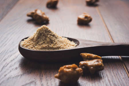 ingradient: Asafoetida cake and powder or Hing or Heeng which is an important ingredient in Indian food recipes with big wooden spoon and mortar, selective focus