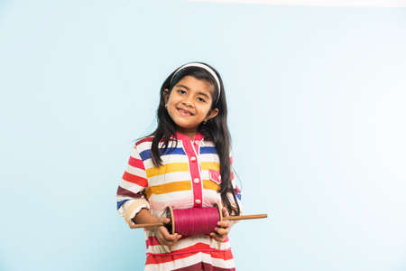 maharashtra: Kite or Patang flying in India, cute and happy little indian girlfemale child holding chakri or wooden spindal and standing over blue background on Makar Sankranti Festival Stock Photo