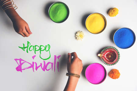 Stock Photo of happy diwali greeting card clicked using elements of Diwali festival like colourful rangoli in bowls, diwali clay lamp or diya and girl or girl making rangoli, writing happy diwali Banque d'images