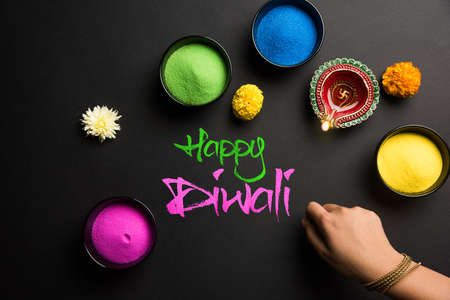 Stock Photo of happy diwali greeting card clicked using elements of Diwali festival like colourful rangoli in bowls, diwali clay lamp or diya and girl or girl making rangoli, writing happy diwali Stock Photo