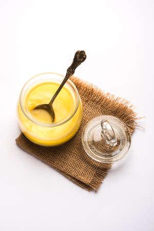 Desi Pure Ghee o mantequilla clarificada en vidrio o recipiente de cobre con cuchara, enfoque selectivo