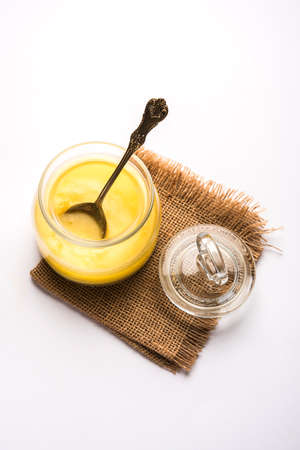 Desi Pure Ghee of geklaarde boter in glas of koperen container met lepel, selectieve focus Stockfoto