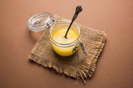 Desi Pure Ghee 또는 숟가락, 선택적 초점이있는 유리 또는 구리 용기의 투명 버터
