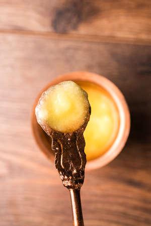 Desi Pure Ghee или осветленное масло в стекле или медный контейнер с ложкой, селективный фокус