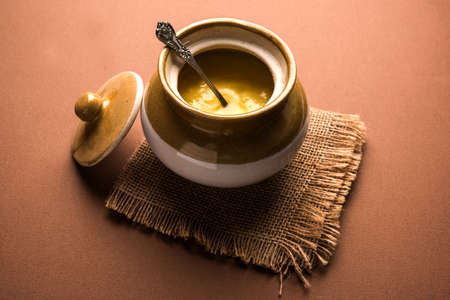 Desi Pure Ghee or clarified butter in glass or Copper container with spoon, selective focus
