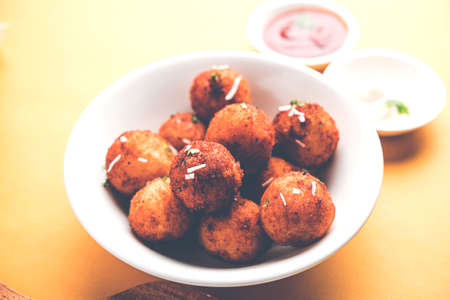 Fried potato cheese balls or croquettes with tomato ketchup. Selective focus