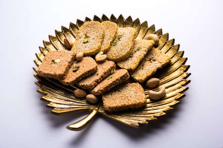 Gajak or til papdi or patti is a dry sweet cake - made of sesame seeds, ground nuts and jaggery, consumed in indian winter especially during Makar Sankranti festival on 14th january