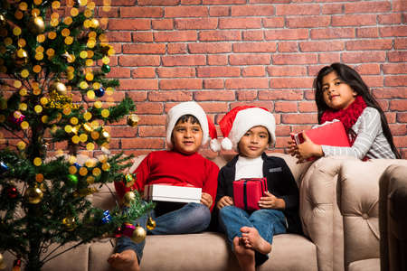 indian kids celebrating christmas with christmas gifts decorating christmas tree and having good time stock
