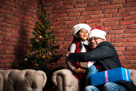 family, holidays, generation, christmas and people concept - smiling Indian grandparents and granddaughter with gift boxes sitting on couch at home or taking selfie or washing television or decorating christmas tree