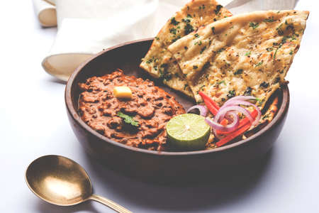Dal makhani or dal makhni is a popular food from Punjab / India made using whole black lentil, red kidney beans, butter and cream and served with garlic naan or Indian bread or roti