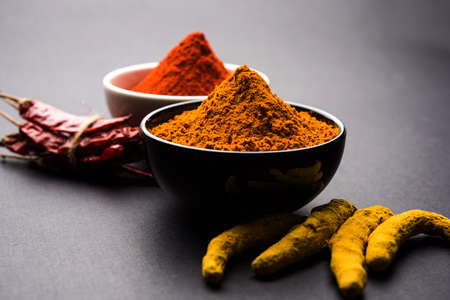 heap of turmeric and red chilli powder in a ceramic bowl on a white or black background Stock Photo