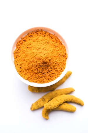 Turmeric powder in ceramic bowl with raw dried turmeric over plain background Reklamní fotografie - 91679493