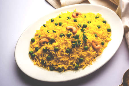Basmati Rice Pilaf or pulav with Peas, or vegetable rice using green peas also known as matar pulav, with added yellow colour, served with plain dal Imagens