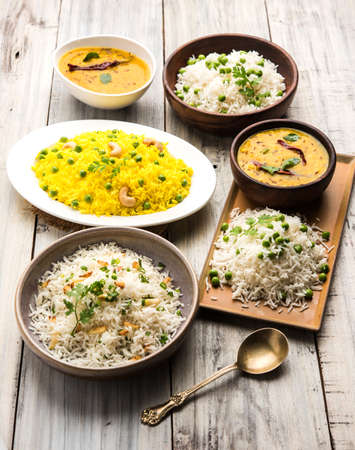 group photo of indian rice with green peas and garlic served with jeera dal fry, selective focus
