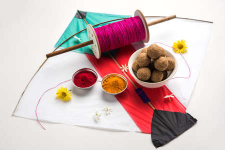 happy Makar Sankranti Festival - Tilgul or Til ladoo in a bowl or plate with haldi kumkum and flowers with Fikri /Reel/Chakri /Spool with colourful thread or manjha and kite over plain background Stock Photo - 92318256