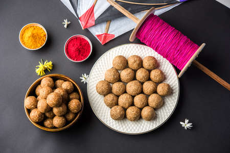 happy Makar Sankranti Festival - Tilgul or Til ladoo in a bowl or plate with haldi kumkum and flowers with Fikri /Reel/Chakri /Spool with colourful thread or manjha and kite over plain background Stock fotó