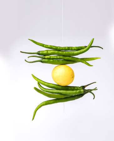 lemon chilies hanging - Indian superstitious lemon and green chillies tied with thread and tied on doors at home or shop to avoid any bad fortune also known as totka or nazar battu 版權商用圖片 - 92318446