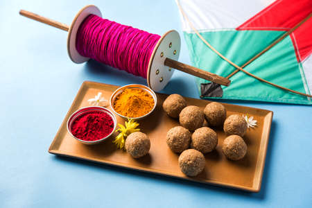 happy Makar Sankranti Festival - Tilgul or Til ladoo in a bowl or plate with haldi kumkum and flowers with Fikri /Reel/Chakri /Spool with colourful thread or manjha and kite over plain background 免版税图像