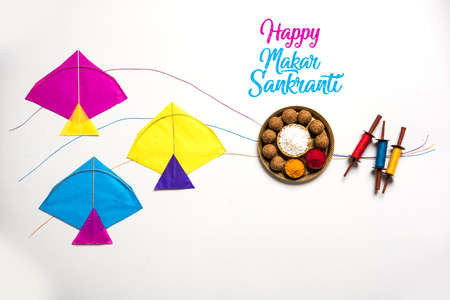 happy Makar Sankranti Festival - Tilgul or Til ladoo in a bowl or plate with haldi kumkum and flowers with Fikri /Reel/Chakri /Spool with colourful thread or manjha and kite over plain background Stockfoto