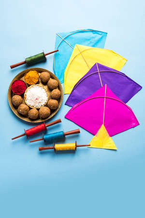 happy Makar Sankranti Festival - Tilgul or Til ladoo in a bowl or plate with haldi kumkum and flowers with Fikri /Reel/Chakri /Spool with colourful thread or manjha and kite over plain background Zdjęcie Seryjne