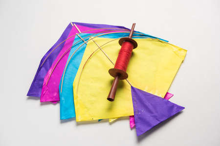 happy Makar Sankranti Festival - Tilgul or Til ladoo in a bowl or plate with haldi kumkum and flowers with Fikri /Reel/Chakri /Spool with colourful thread or manjha and kite over plain background 스톡 콘텐츠