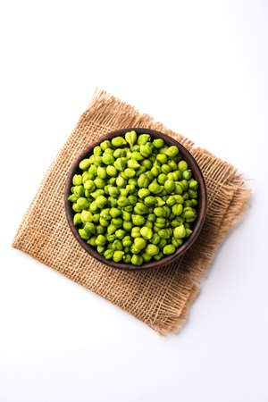 Fresh Green Chickpeas or Chick peas also known as harbara or harbhara in hindi and Cicer is scientific name, served in a wooden bowl or plate. selective focus