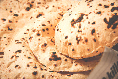 Roti or chapati making machine, selective focus. Indian ready to eat Indian flat bread coming out of machine Stock Photo