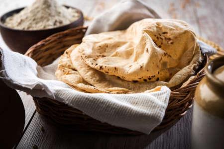 Indisches Brot / Chapati / Fulka / Gehu Roti mit Weizenkörnern im Hintergrund. Es ist ein gesundes faserreiches traditionelles nord- / südindisches Essen, selektiver Fokus