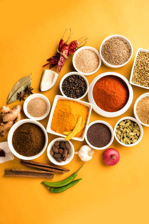 Raw Indian Spice Powder over red, yellow or green  background, selective focus Stock Photo
