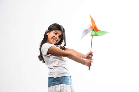 indian girl with paper windmill toy made up of tricolour or indian flag colours. Saluting, looking at camera or with red heart toy, celebrating 26 January republic day or 15 august independence day Stock Photo