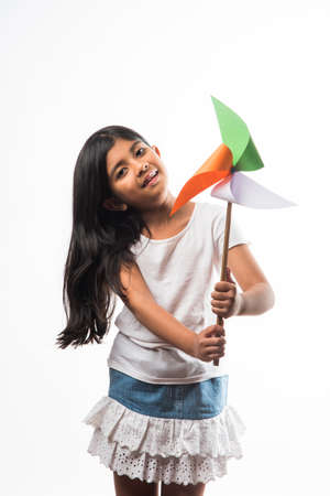indian girl with paper windmill toy made up of tricolour or indian flag colours. Saluting, looking at camera or with red heart toy, celebrating 26 January republic day or 15 august independence day