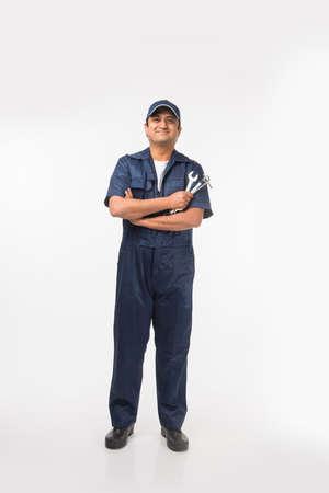 Mécanicien automobile heureux indien en costume bleu et capuchon tenant l'outil clé en action, isolé sur fond blanc