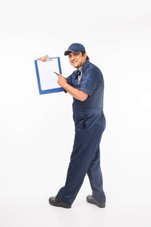 Indian happy auto mechanic in blue suit and cap holding spanner tool in action, isolated over white background