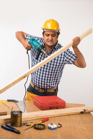 Handsome Indian Carpenter or wood worker in action, isolated over white background Stock Photo