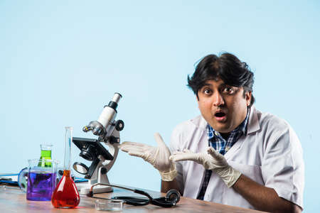 AsianIndian male scientist or doctor or science student experimenting with microscope and chemicals, laptop and smartphone in a lab Stock Photo