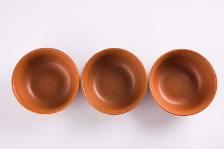Empty terracotta serving bowl or brown clay soup bowl isolated on white Stock Photo