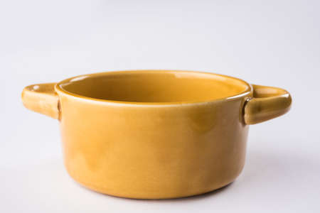 Empty yellow ceramic serving bowl, isolated over white or gray background
