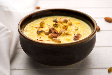 kheer or rice pudding is an Indian dessert in a brown terracotta bowl with dry fruits toppings