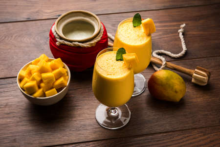 Mango Lassi or smoothie in big glass or small bottles with curd, cut fruit pieces and blender. Moody background, selective focus Archivio Fotografico