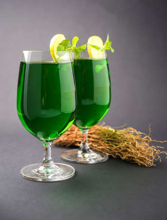 Green KHUS Sharbat or Vetiver grass extract or Chrysopogon zizanioides served in tall glass with mint leaf, popular summertime refreshing drink from India
